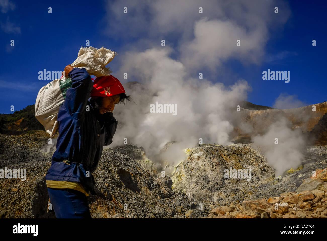 Man passes through crater ridge of Mount Papandayan, West Java, Indonesia. © Reynold Sumayku - Stock Image