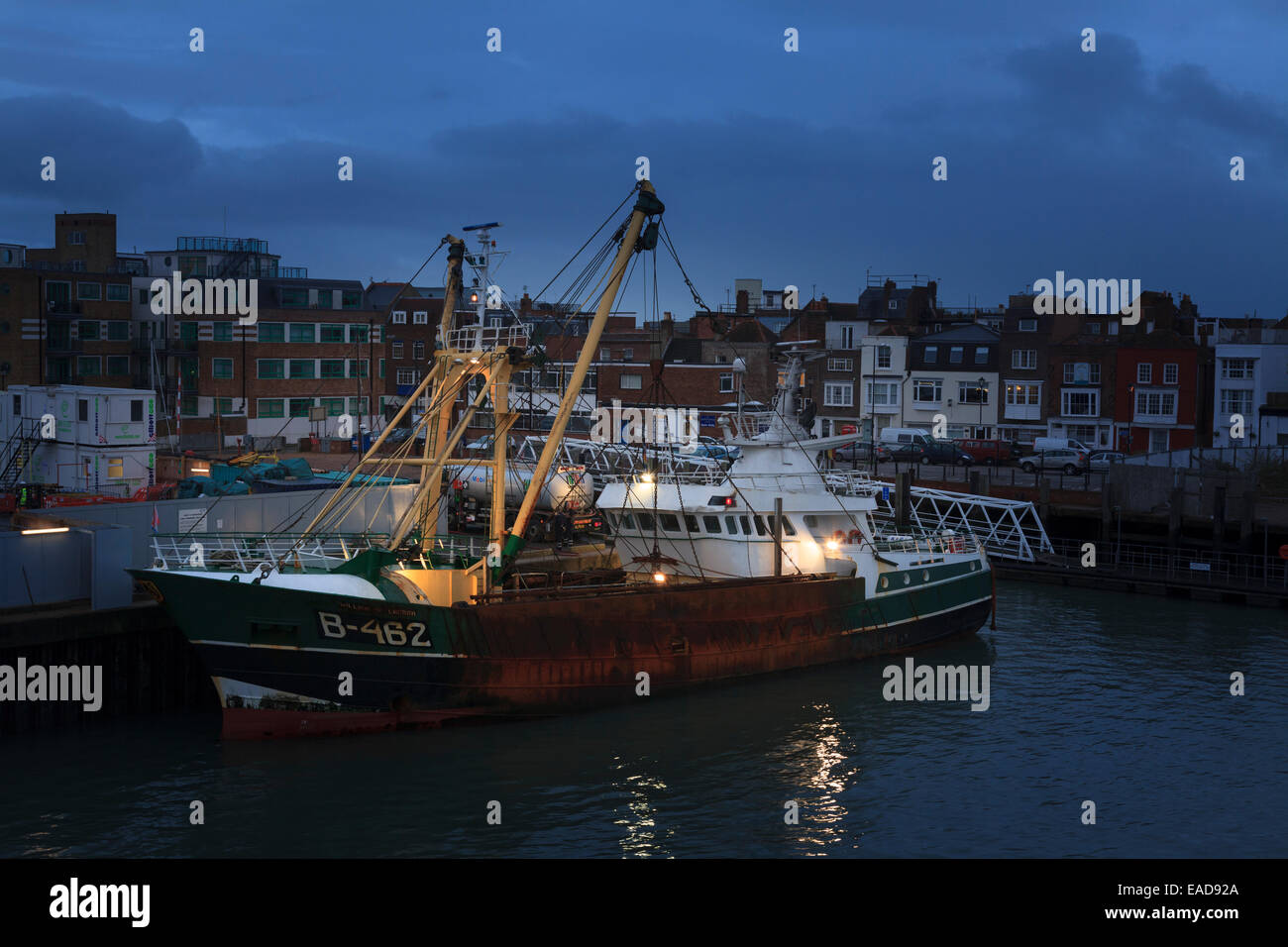 Trawler moored in Portsmouth Harbour with working lights in the pre dawn Stock Photo
