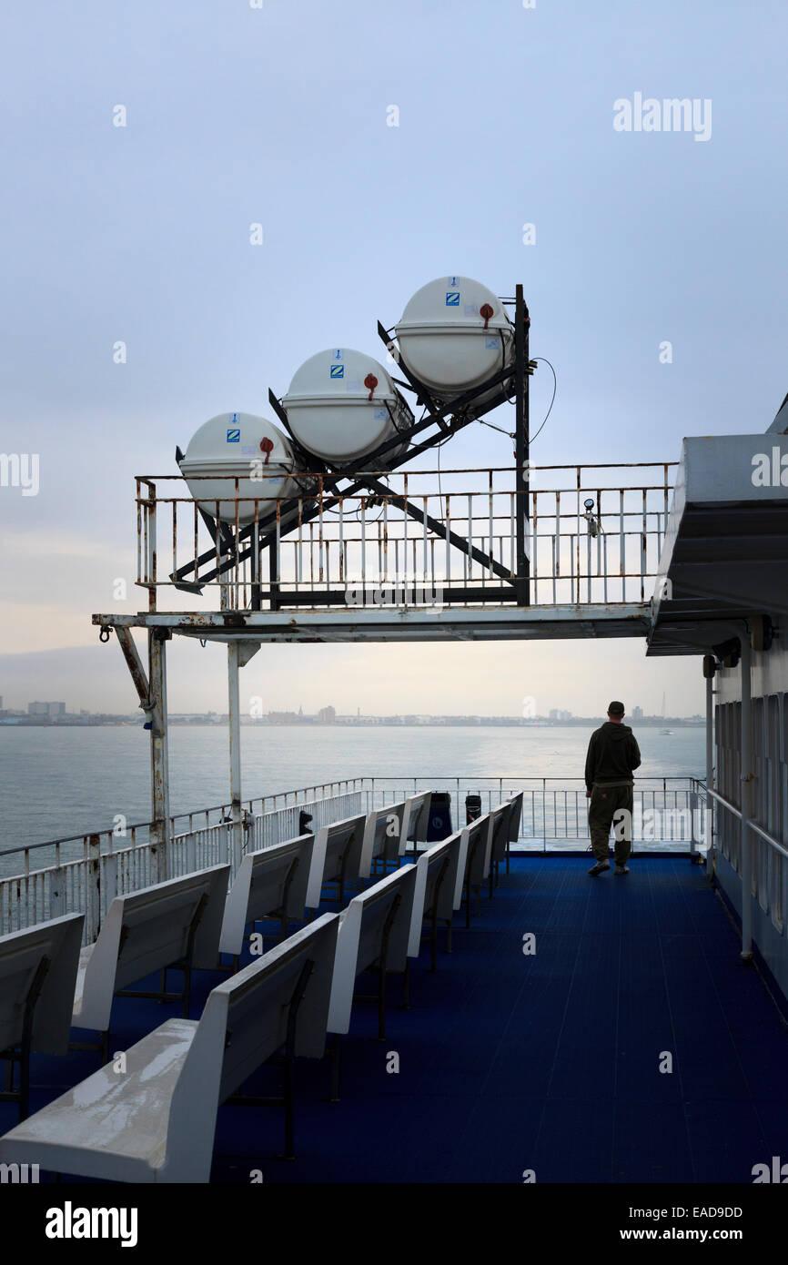 Man on car ferry deck under Zodiac Liferaft deployment slide - Stock Image