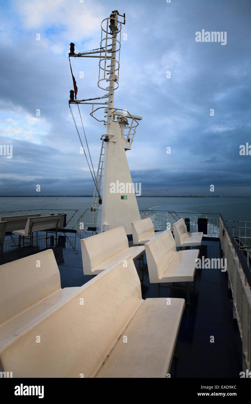 Unoccupied upper deck seats on ferry with ships mast and hoop vertical access ladder Stock Photo