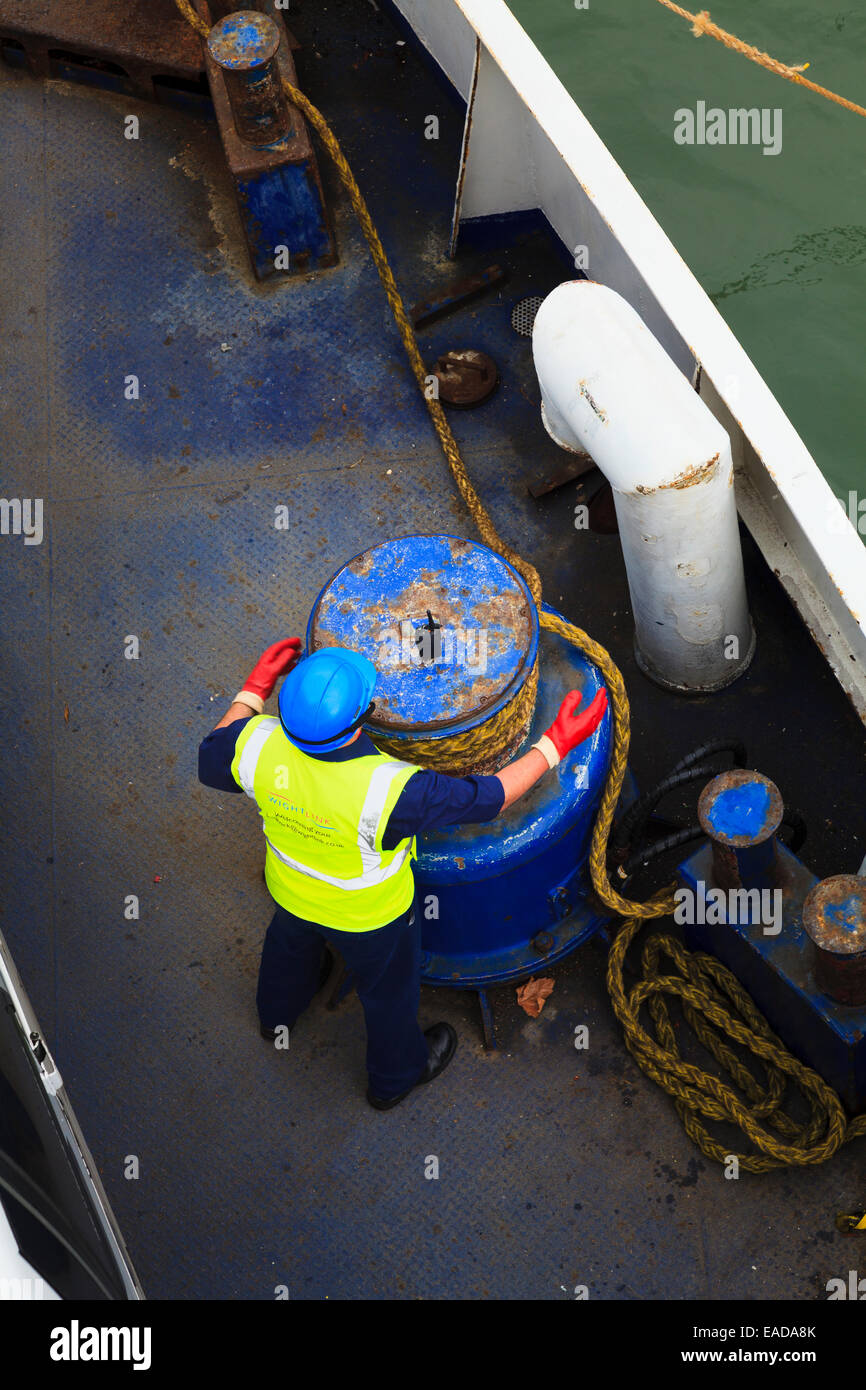 Looking down on crew member using mooring rope winding winch - Stock Image
