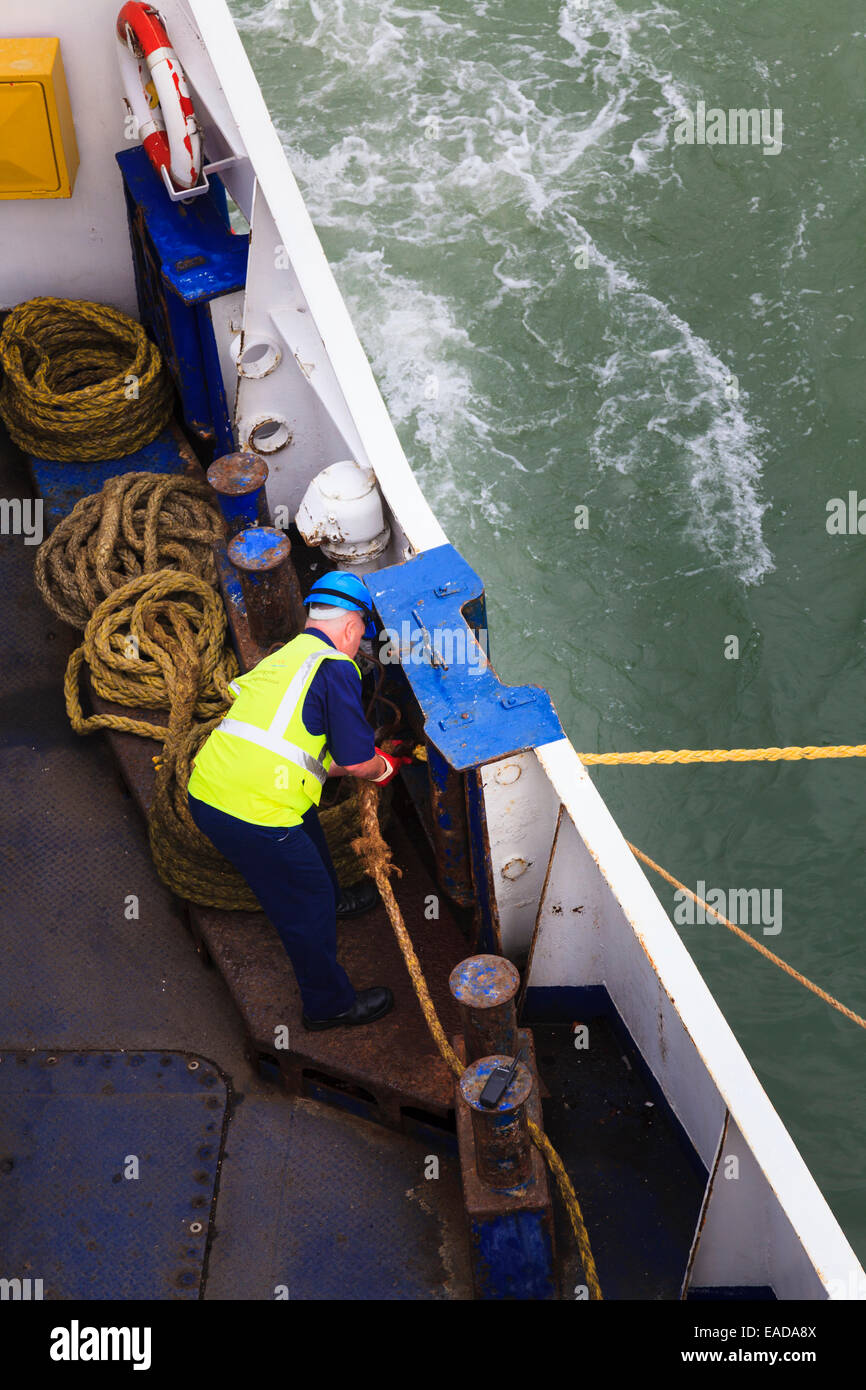 Looking down on crew member using mooring rope winding winch Stock Photo