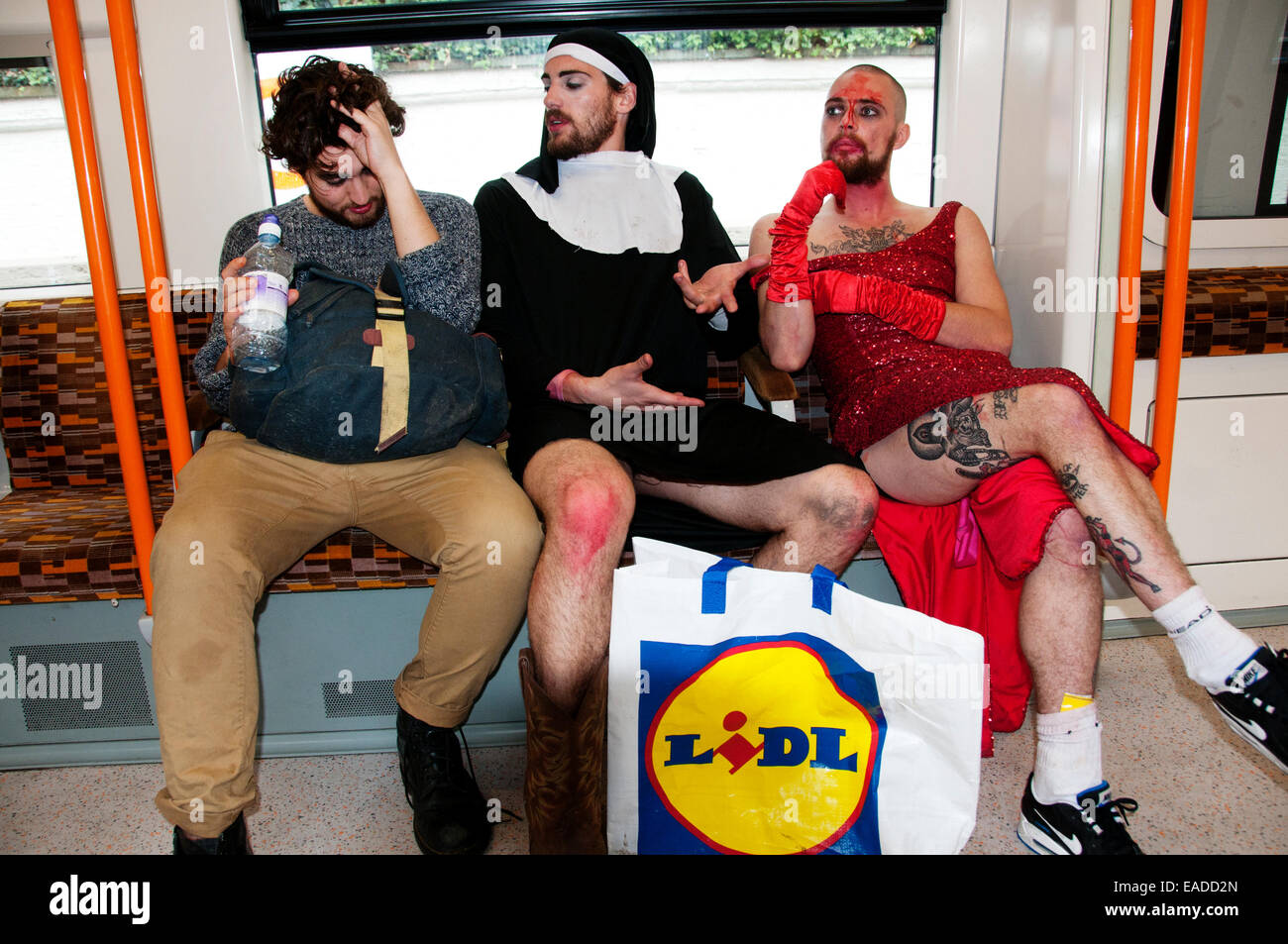 London Overground. Post Halloween party goers one in a nun's habit, another in a red dress return home after - Stock Image