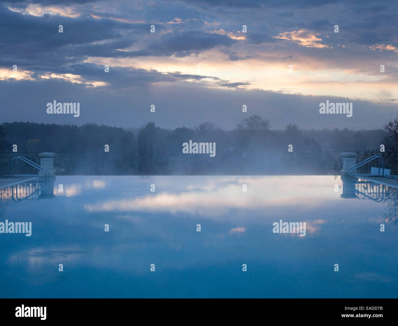 country side with Infinity pool at dawn with fog - Stock Image