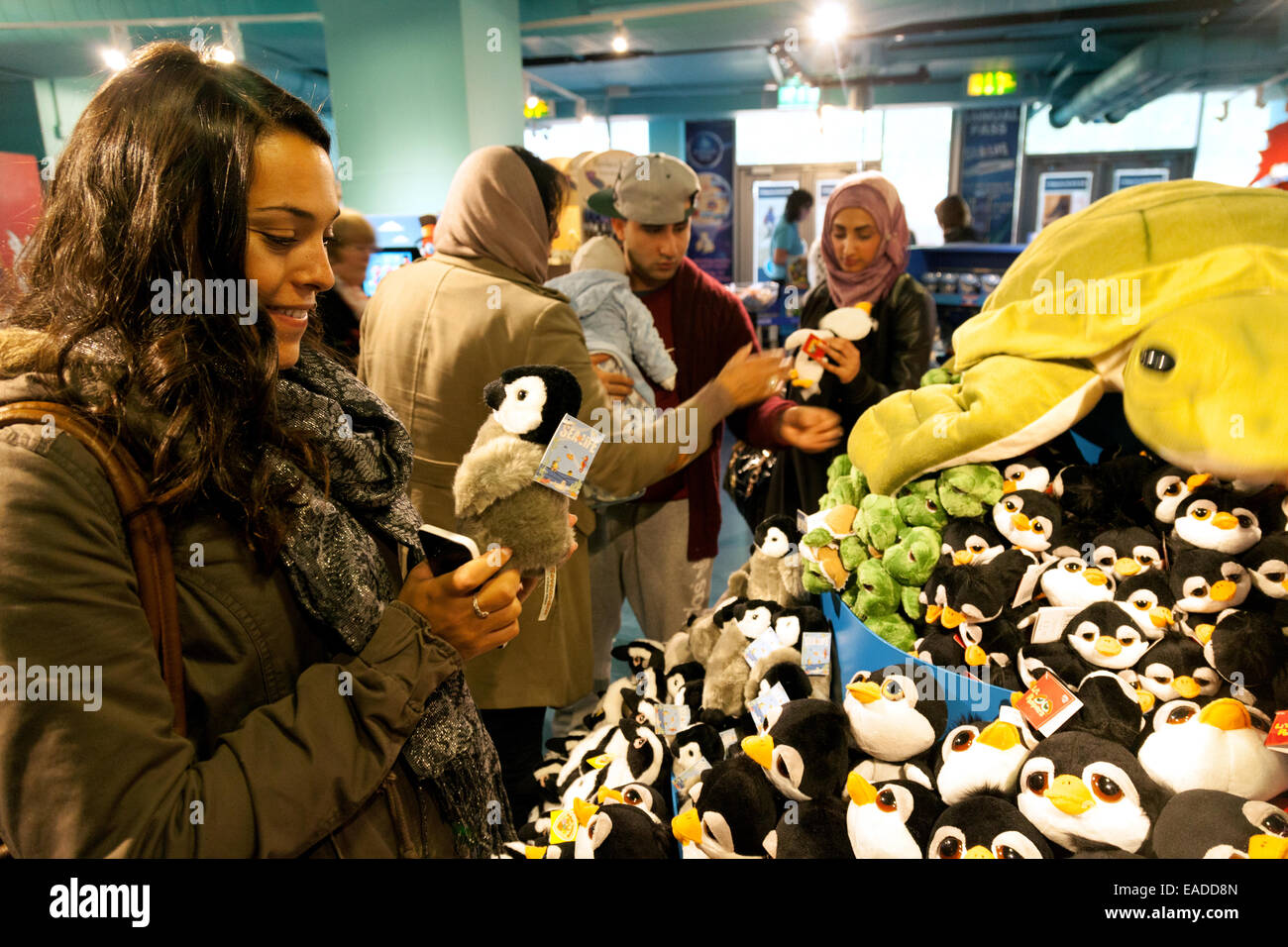 A young woman shopping in the gift shop, The National Sealife Centre, Birmingham UK - Stock Image