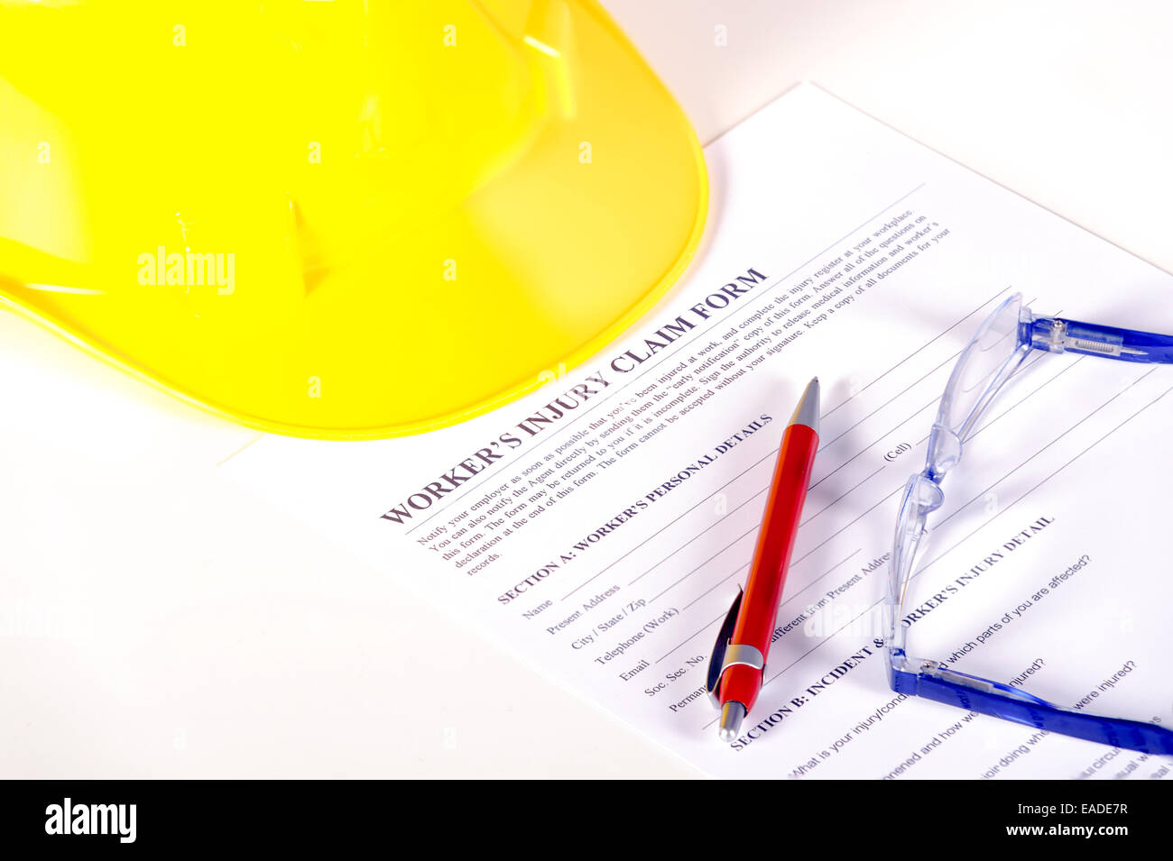 Worker injury claim hard hat with eyeglasses and pen on white background - Stock Image