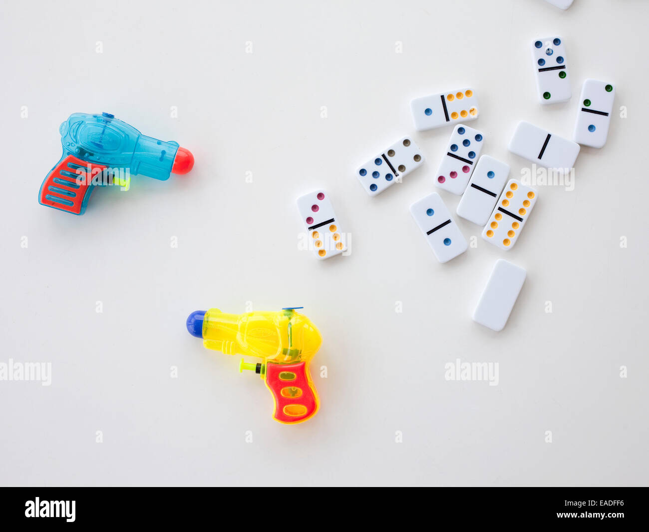 dominoes and water pistols - Stock Image