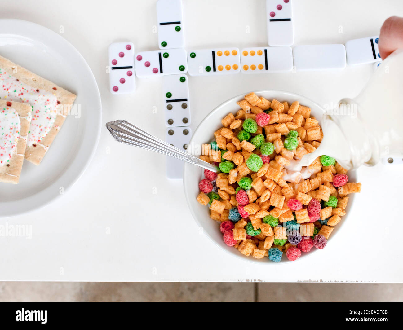 pouring milk on breakfast cereal - Stock Image