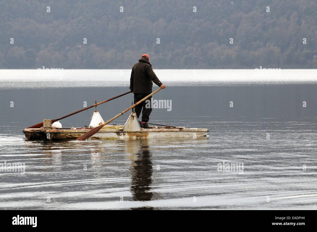 Pescador trabajando en un lago italiano. - Stock Image