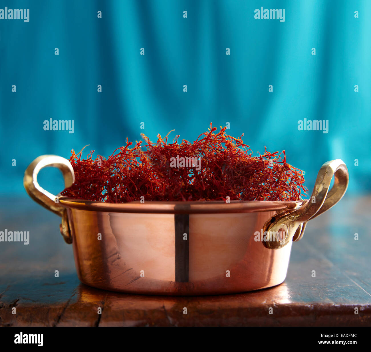 Saffron in a copper pot on a wood table - Stock Image