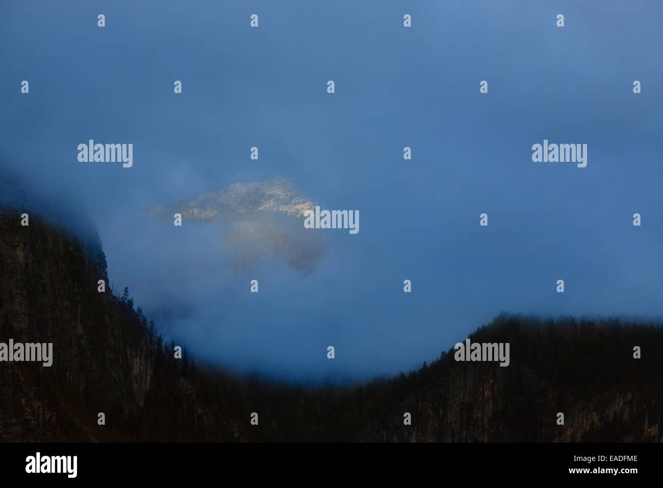Mountain peak illuminated by beams of a rising sun in clouds gap - Stock Image