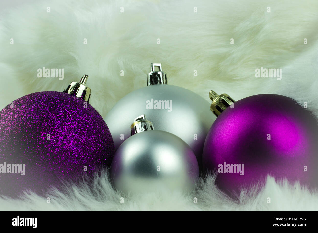 purple and silver christmas decorations on white fur
