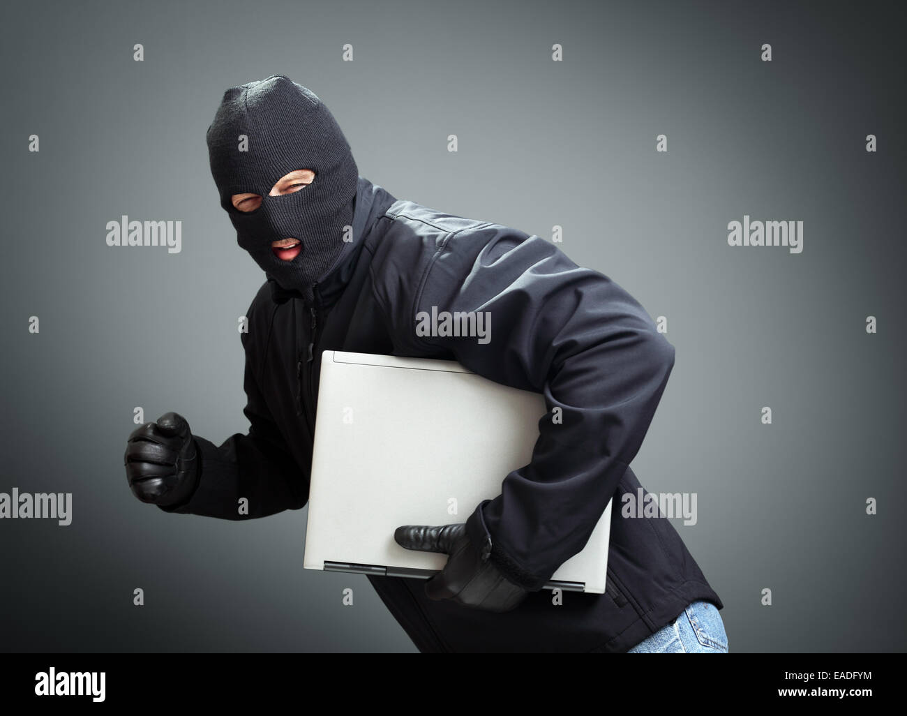 Thief stealing laptop computer - Stock Image