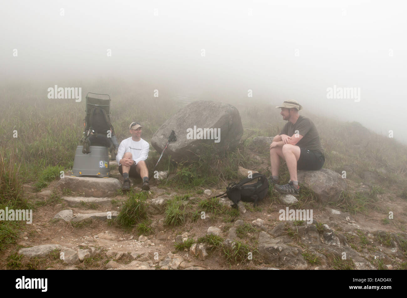 Hikers take a break on the way up to Sunset Peak, Tai Tung Shan, located on Lantau Island Hong Kong China - Stock Image