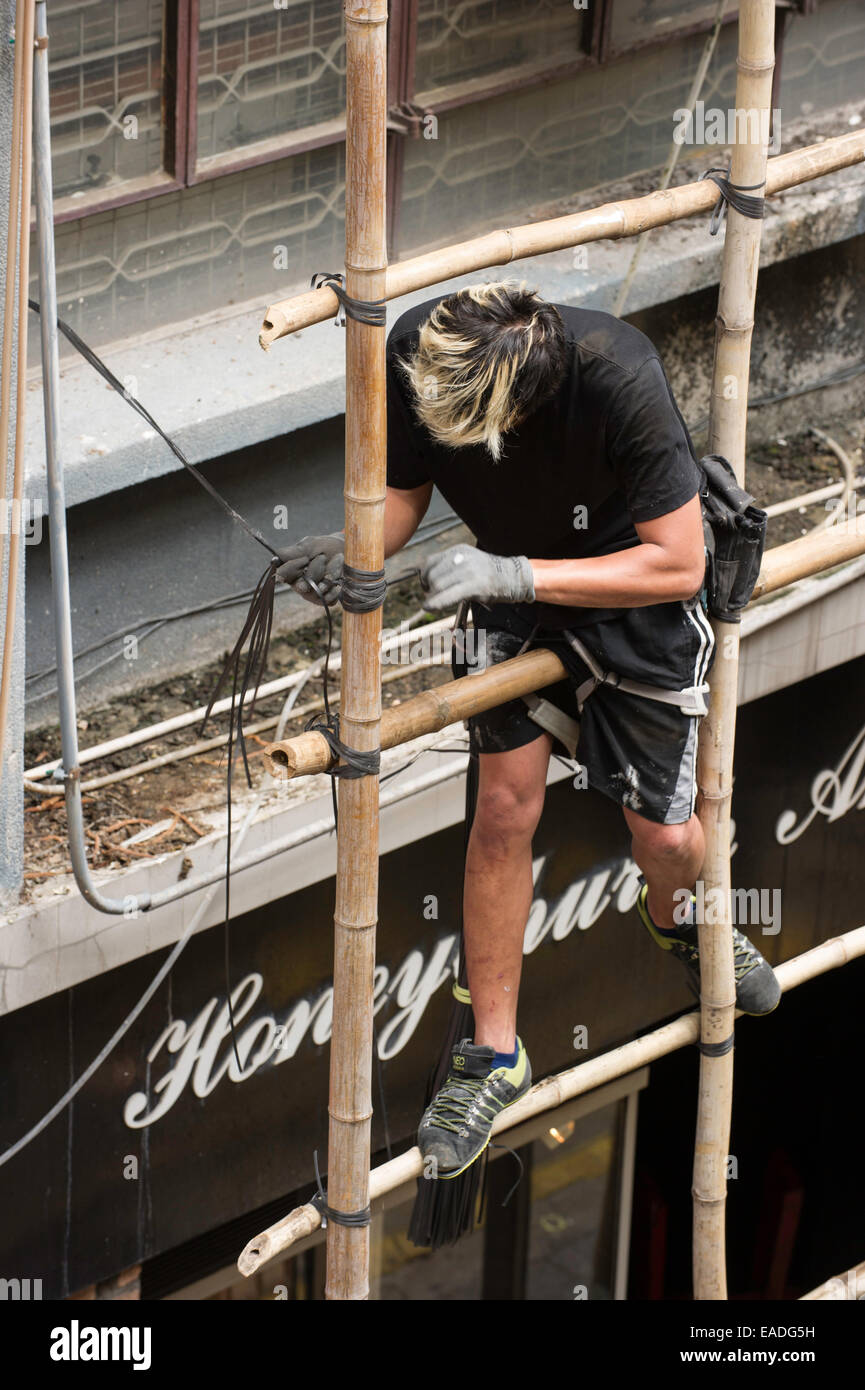 Man building scaffolding by tying lengths of bamboo together, Hong Kong. - Stock Image