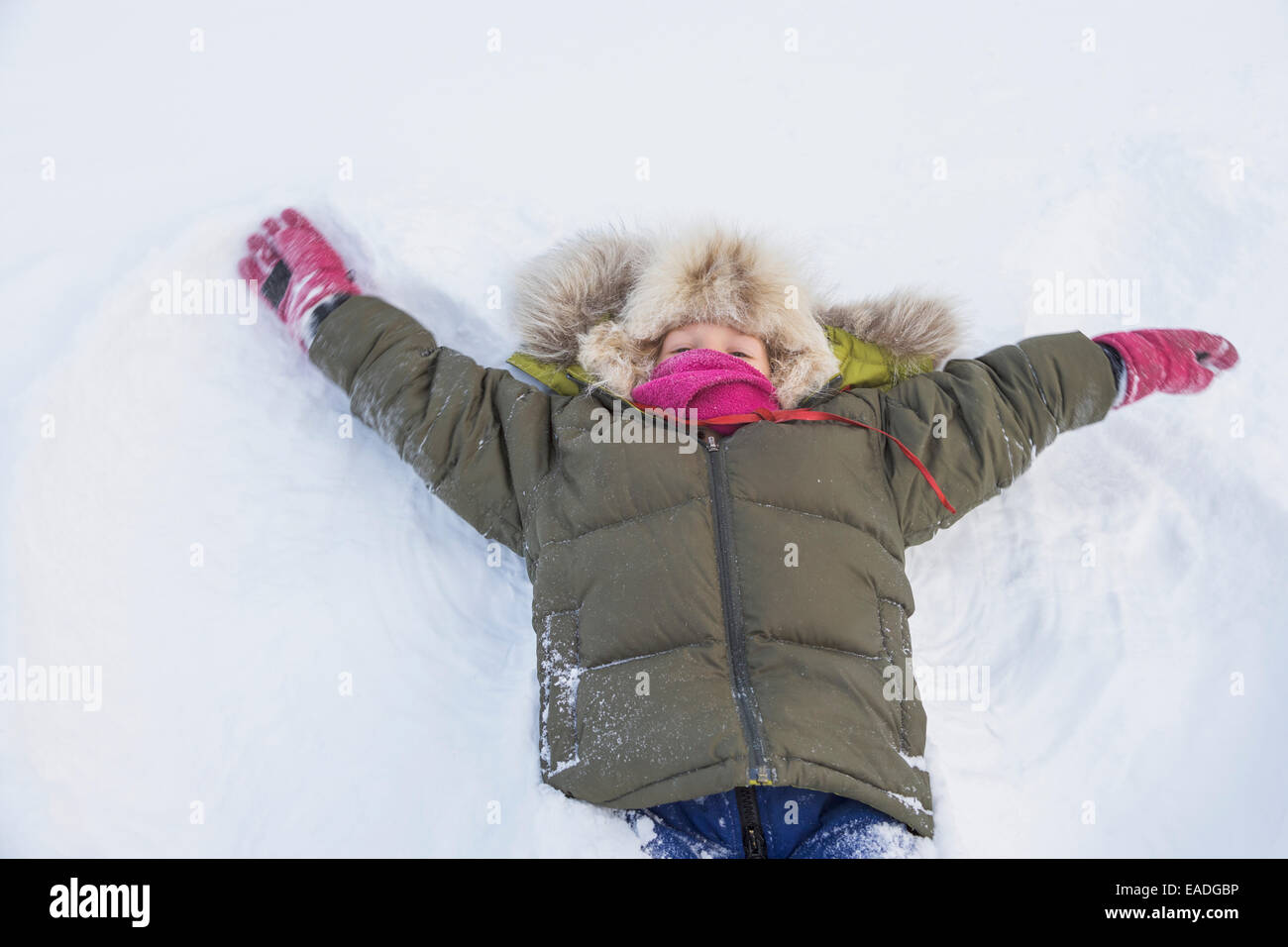 Young boy dressed in a winter parka with a wolf ruff makes a snow angel in Wiseman, Alaska, Arctic - Stock Image