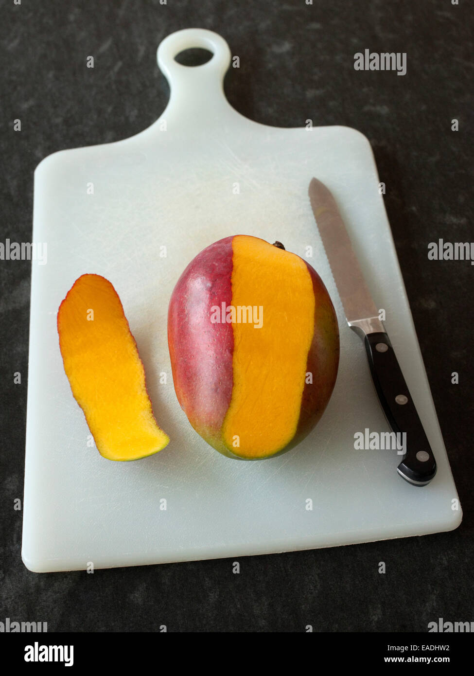 partially peeled mango and knife on cutting board - Stock Image