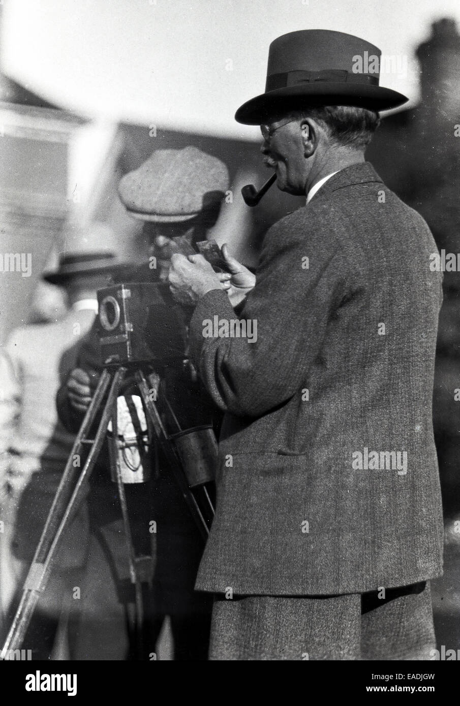 1930s, Historical picture showing a photographer and assistant camera and tripod checking the glass plate of the - Stock Image