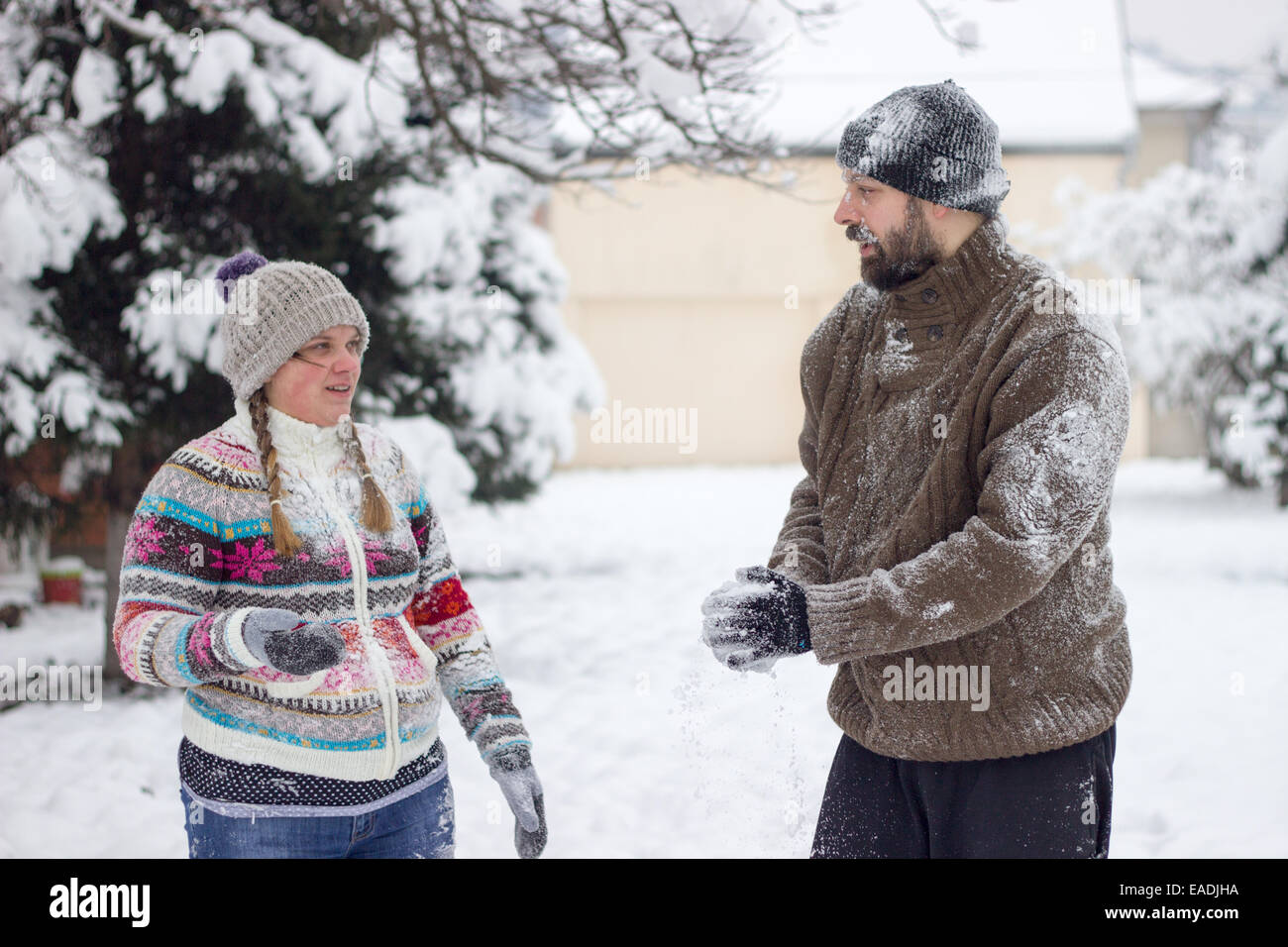 Cute young hipster couple covered in snow in the middle of a snowball fight - Stock Image