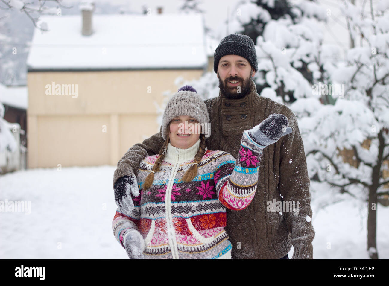 Cute hipster couple covered in snow, enjoying winter vacation - Stock Image
