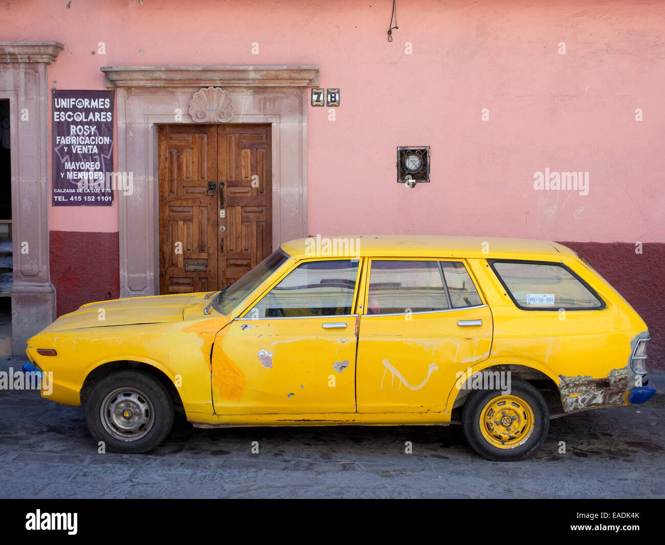 Old yellow car on cobblestone street in Mexican Village - Stock Image