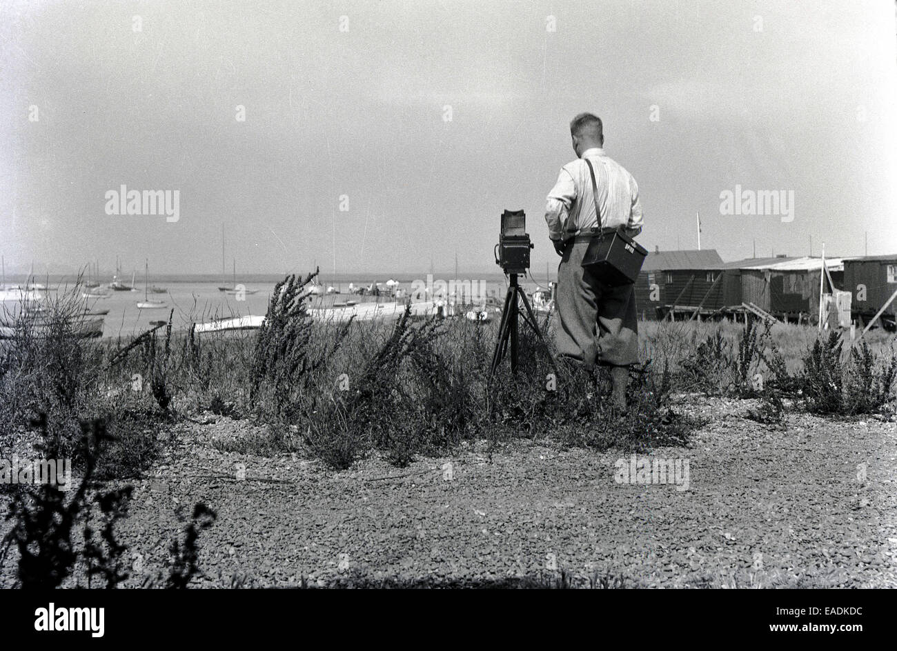 1930s, Historical picture of a male photographer using a camera and tripod to take a picture of the Norfolk sea - Stock Image