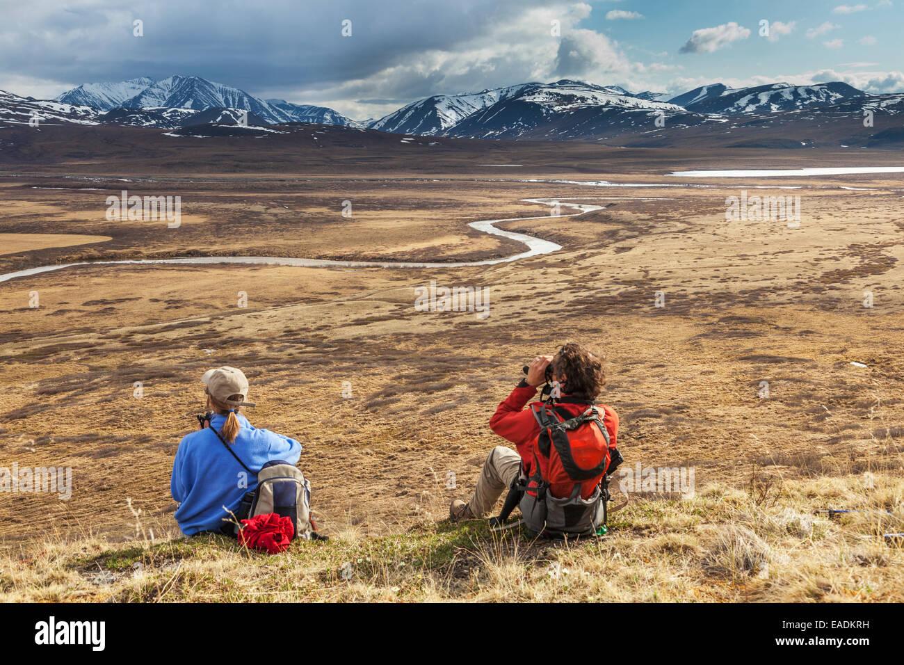 Hikers enjoy view of the Nigu river, Brooks range, Gates of the Arctic National Park, Alaska. Stock Photo