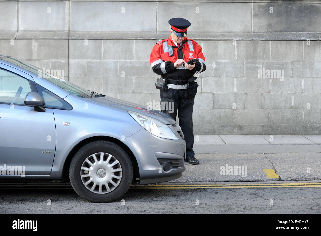 A traffic warden issues a parking ticket to an illegally parked car. - Stock Image