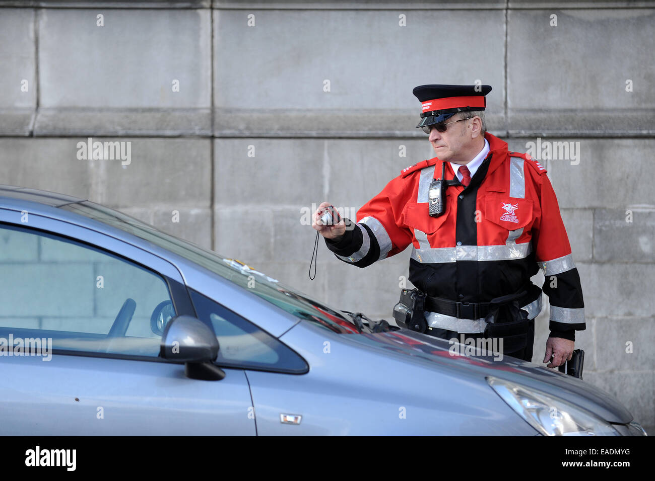 A traffic warden photographs a car after issuing a parking ticket for illegal parking. - Stock Image
