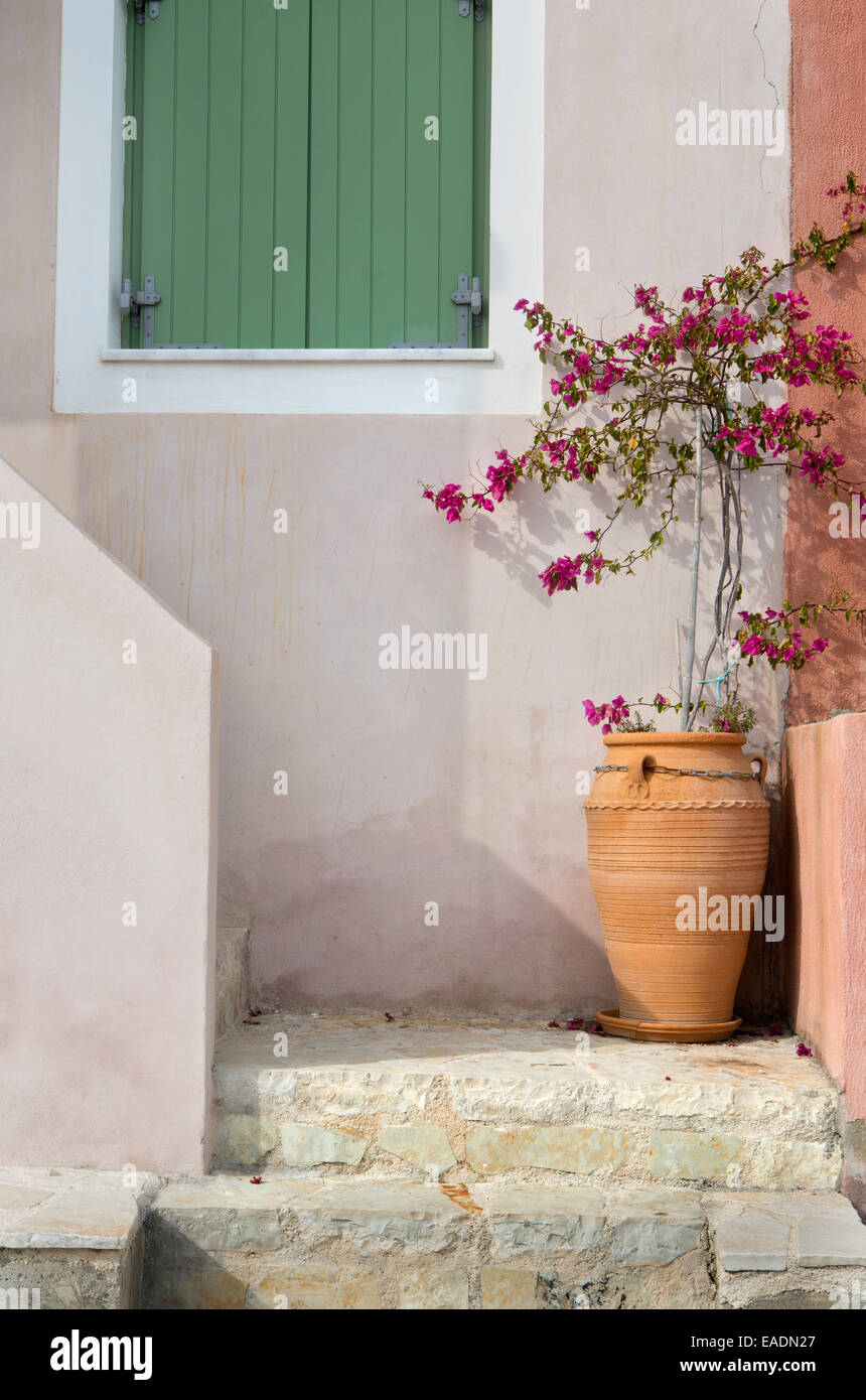 A Greek urn containing pink flowers on the steps of a house in Assos, Kefalonia. Stock Photo