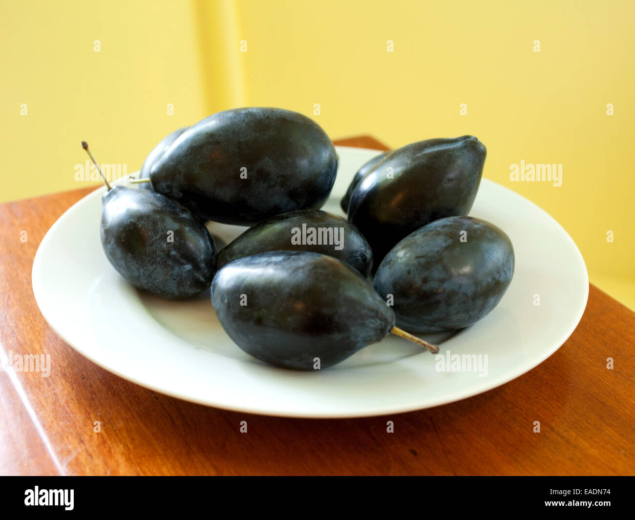 Black Plums On White Plate In Kitchen - Stock Image