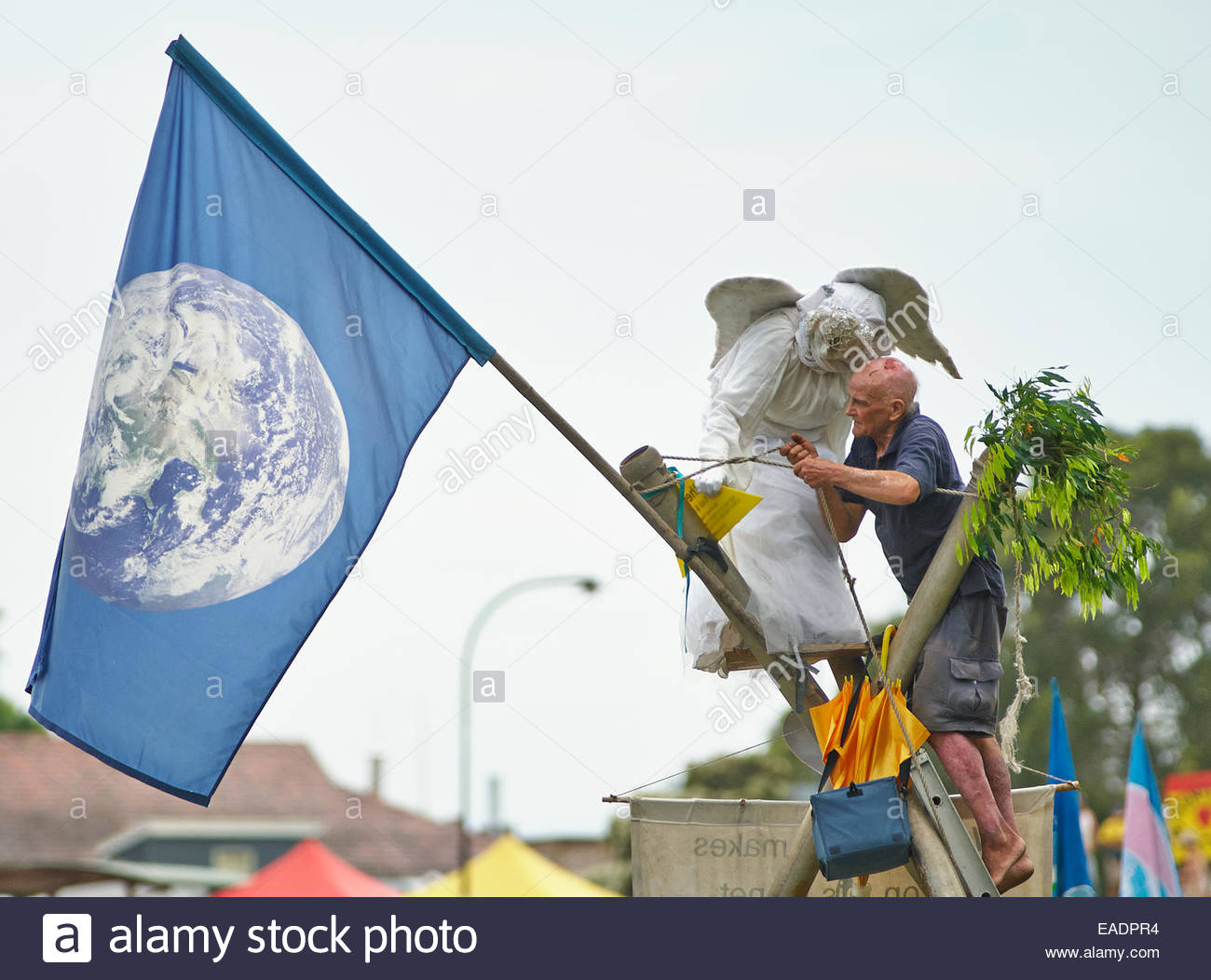 the earth angel and a man tying ropes atop a bamboo tripod at the 'gasfield free northern rivers' declaration, - Stock Image