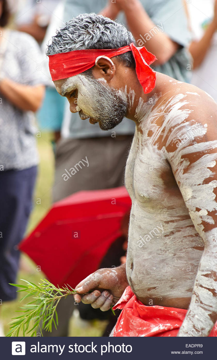 An Australian Aboriginal man in white body paint and red bandana, holding a symbolic tree branch, at the 'gasfield - Stock Image