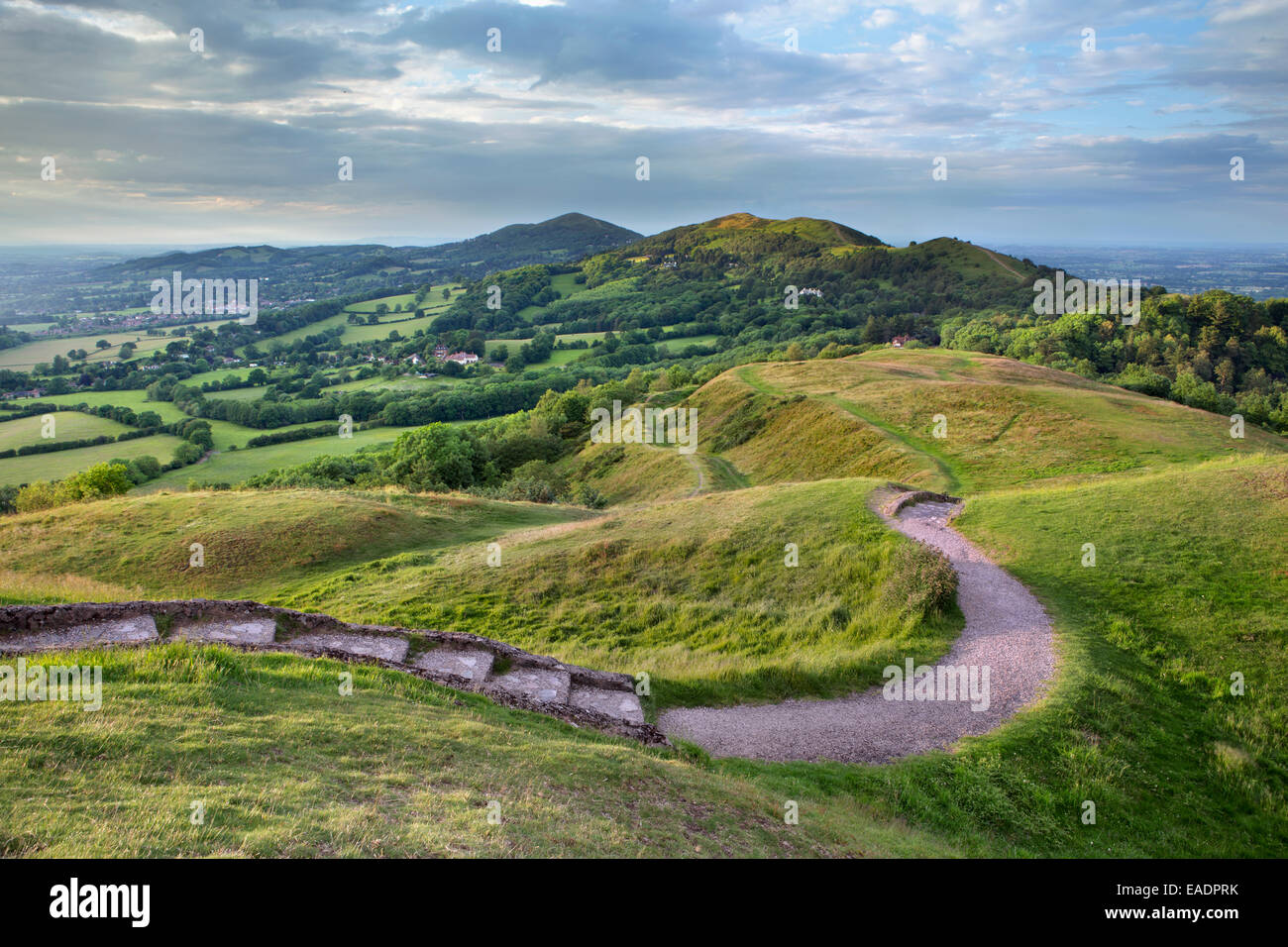 The ramparts of the historic hill fort of British Camp, Herefordshire Beacon, are lit up with the strong light from - Stock Image