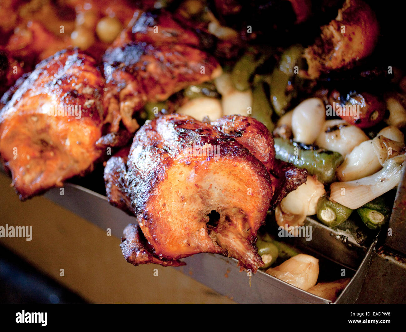 Chicken roasting on spigot with various vegetables - Stock Image