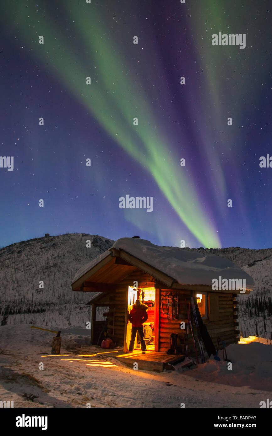 Alaska,Log Cabin,Northern Lights,Green,Woman - Stock Image