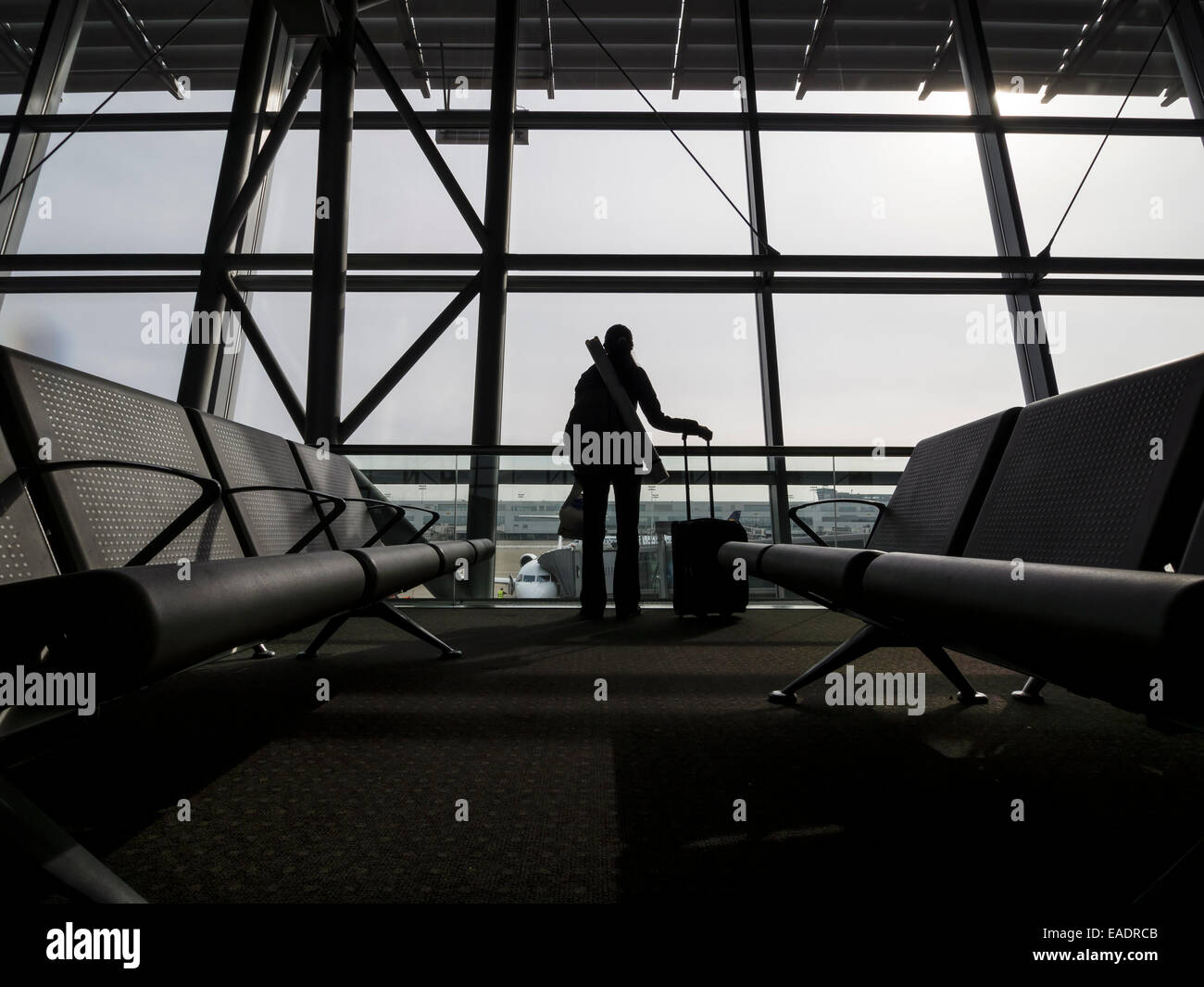 Silhouette of a person with a rolling suitcase in front of an airport terminal window - Stock Image