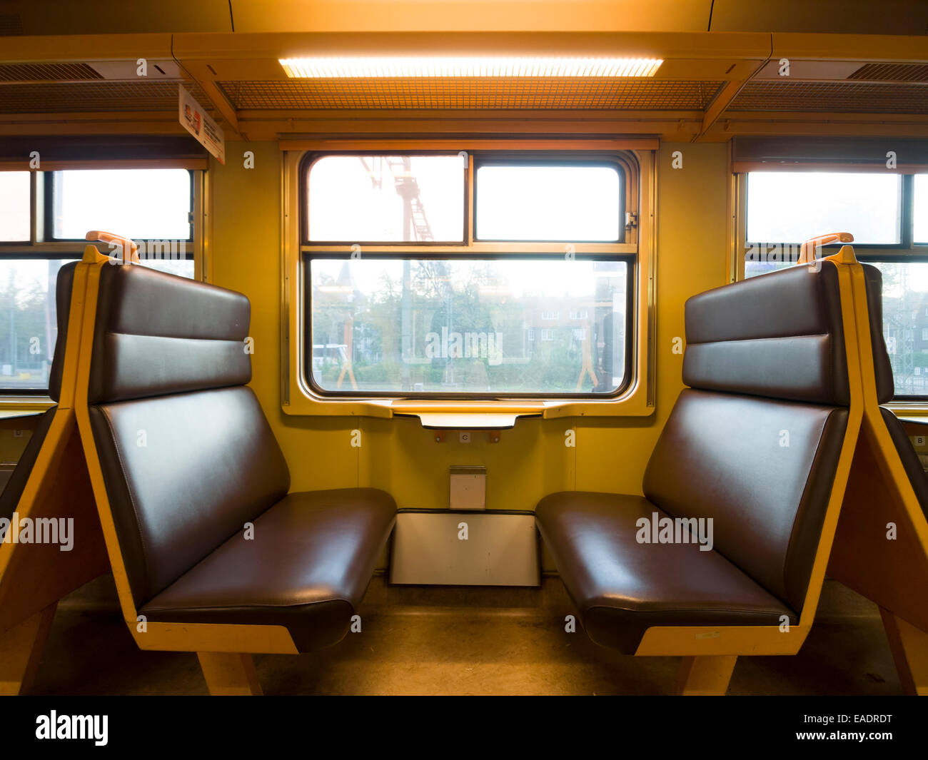 Train carriage with empty seats face to face Stock Photo