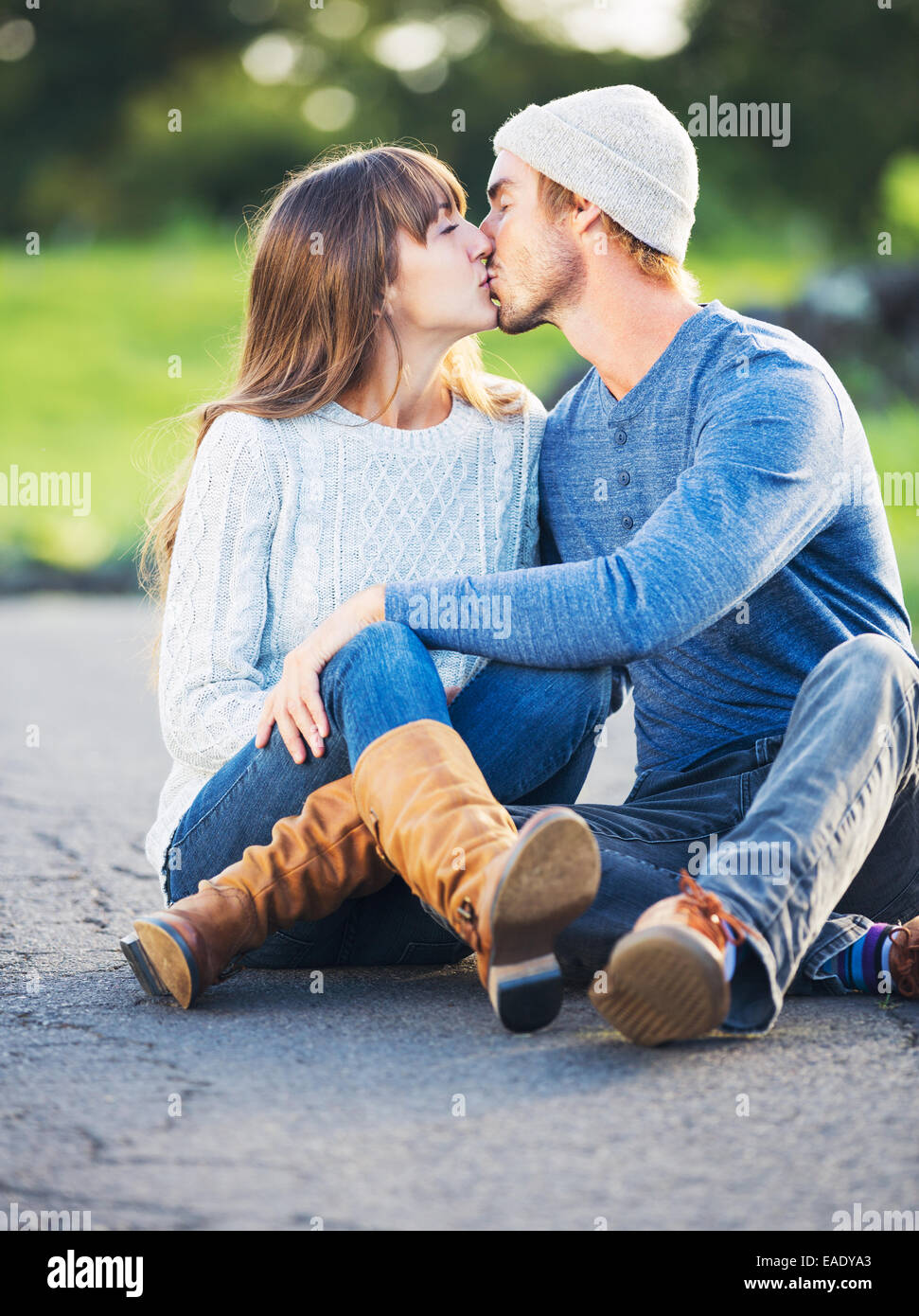 Happy Young Couple Having Fun Outdoors. Romantic Couple Kissing in Love on Country Road. - Stock Image