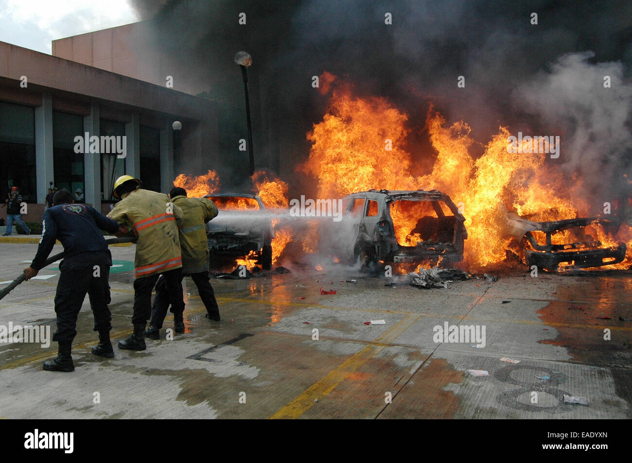 Chilpancingo, Mexico. 12th Nov, 2014. Firefighters try to suffocate the fire in vehicles in the parking of Guerrero's Stock Photo