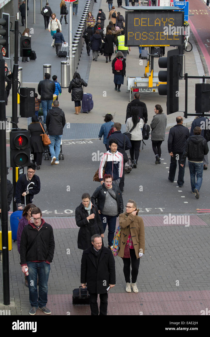 Commuters outside  Kings Cross station with delays possible sign - Stock Image