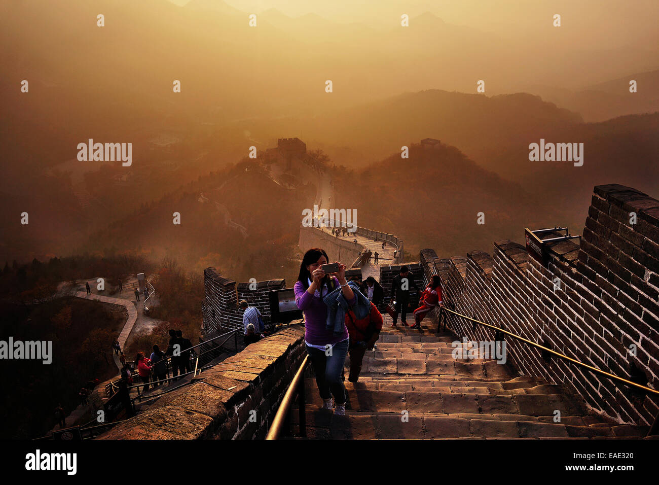The Great Wall of China rises at sunset above the surrounding landscape overcast by smog at Badaling, some 70kilometers - Stock Image