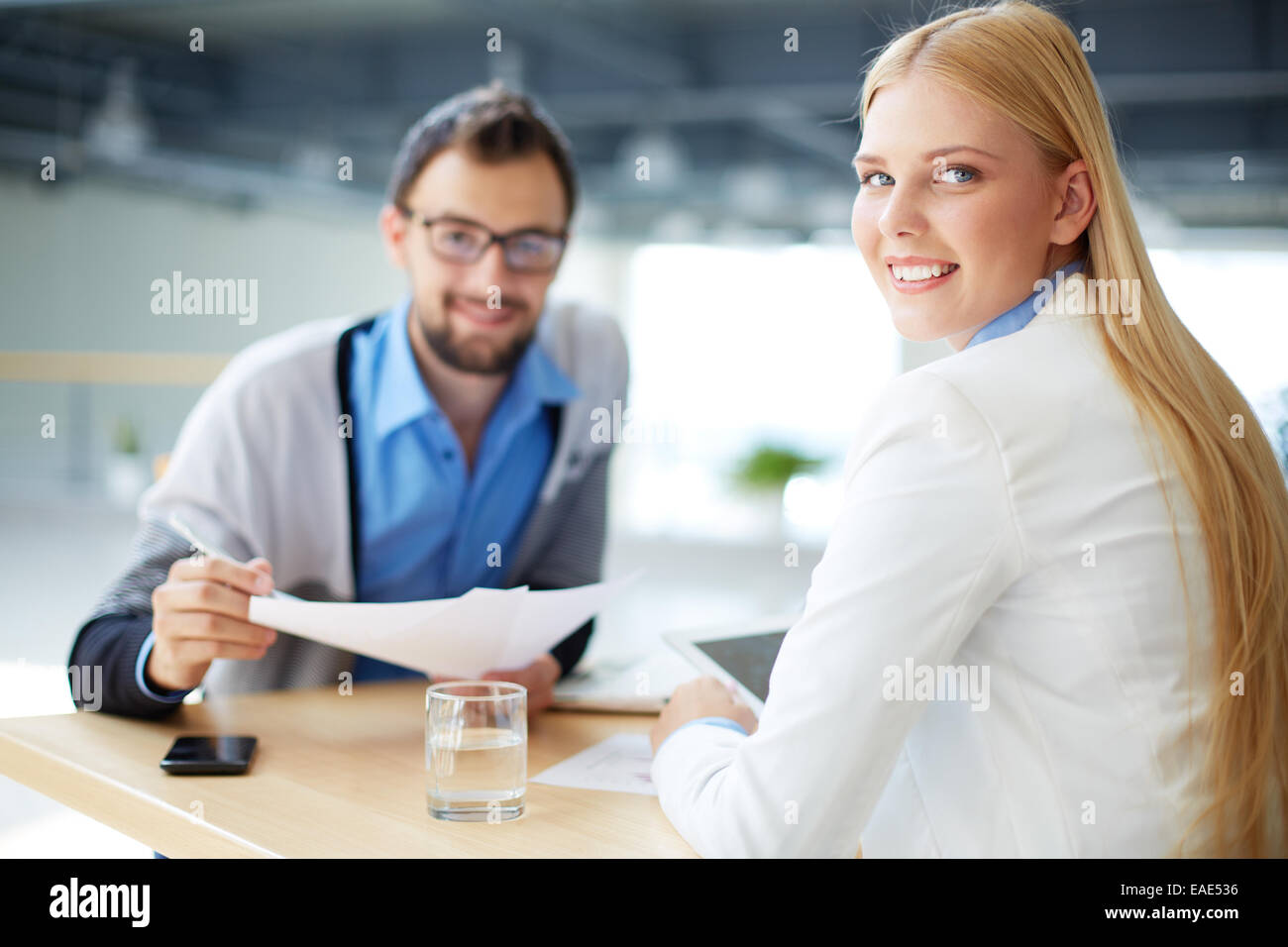 Friendly businesswoman looking at camera with her co-worker on background - Stock Image