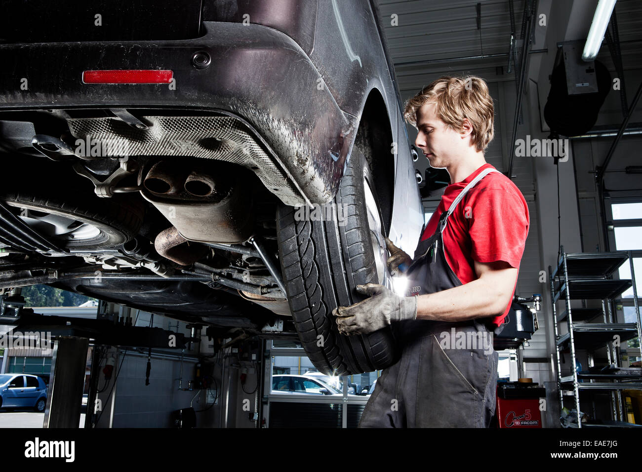 Car mechanic changing tyres in a car repair shop, St.Gertraudi, Reith im Alpbachtal, Kufstein District, North Tirol, - Stock Image