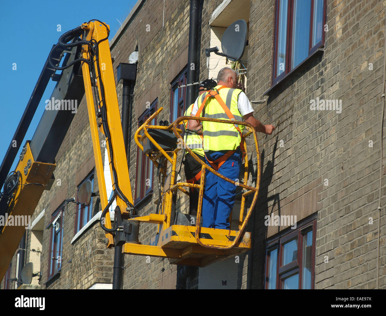 Tradesmen cement pointing the the exterior of a building hoisted up upon a cheery picker vehicle for easy access - Stock Image