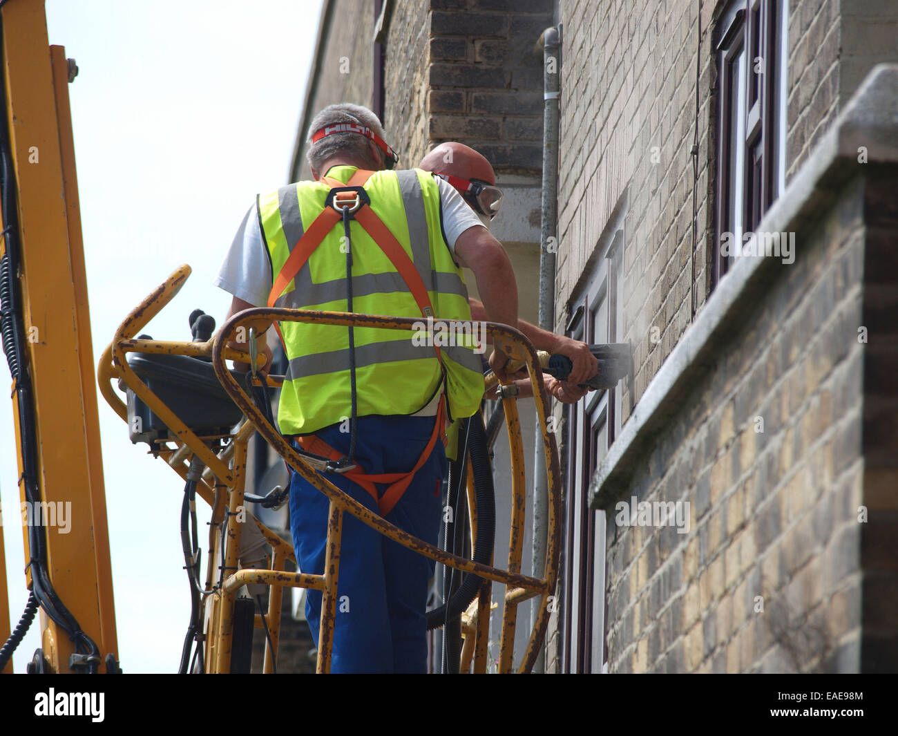 Tradesmen cement pointing the exterior of a building hoisted up upon a cheery picker vehicle for easy access nearer - Stock Image