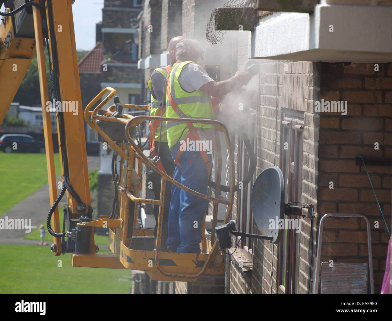 Tradesmen cement pointing the exterior of a building hoisted up upon a cherry picker vehicle for easy access to - Stock Image