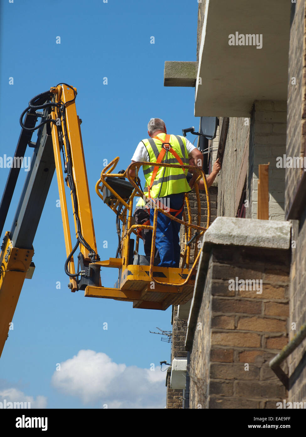 Tradesmen cement pointing the exterior of a building hoisted up upon a cherry picker vehicle for easy access nearer - Stock Image