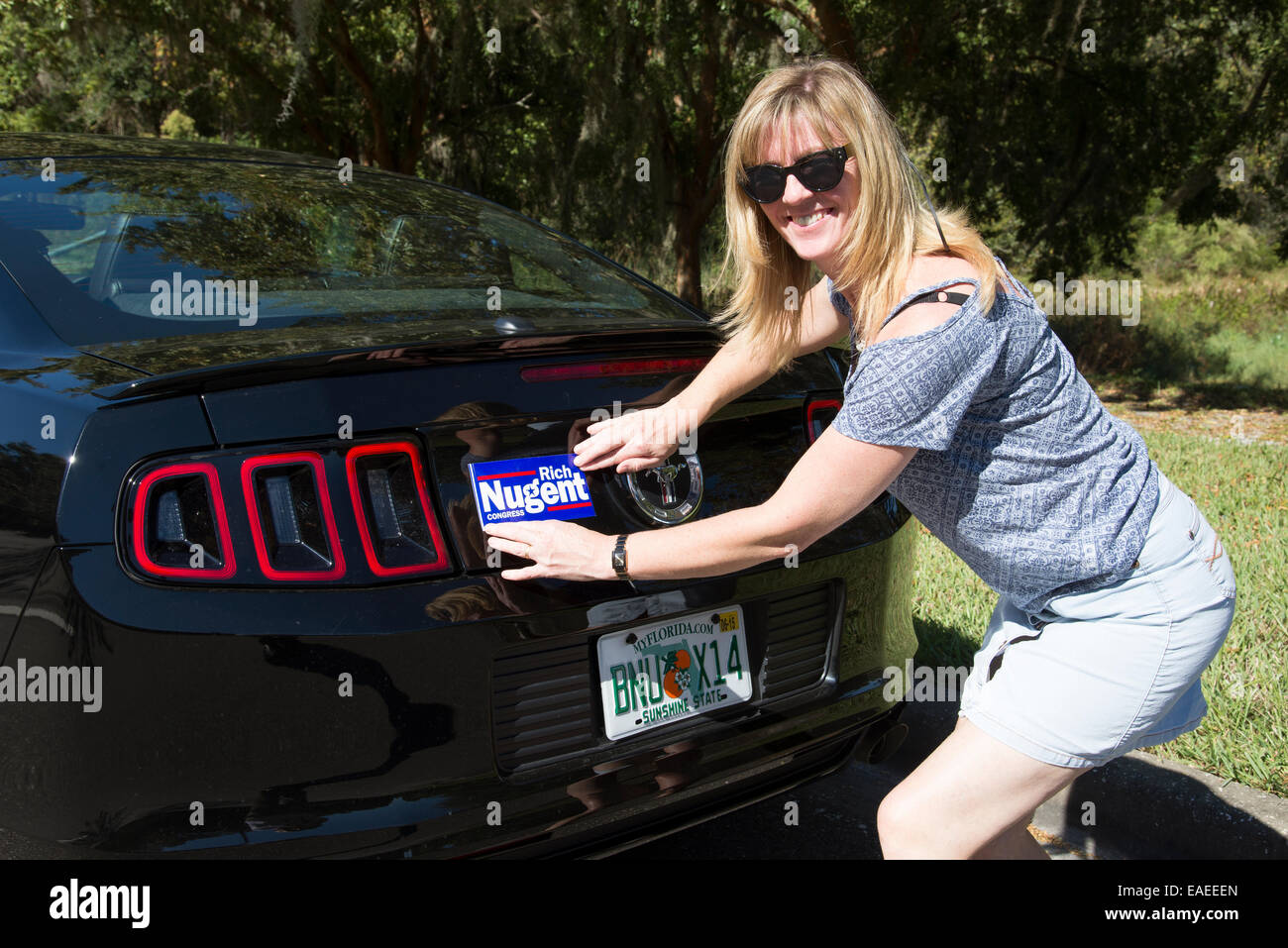 Political supporter puts bumper sticker on her American car Rich Nuggent congressman elect - Stock Image