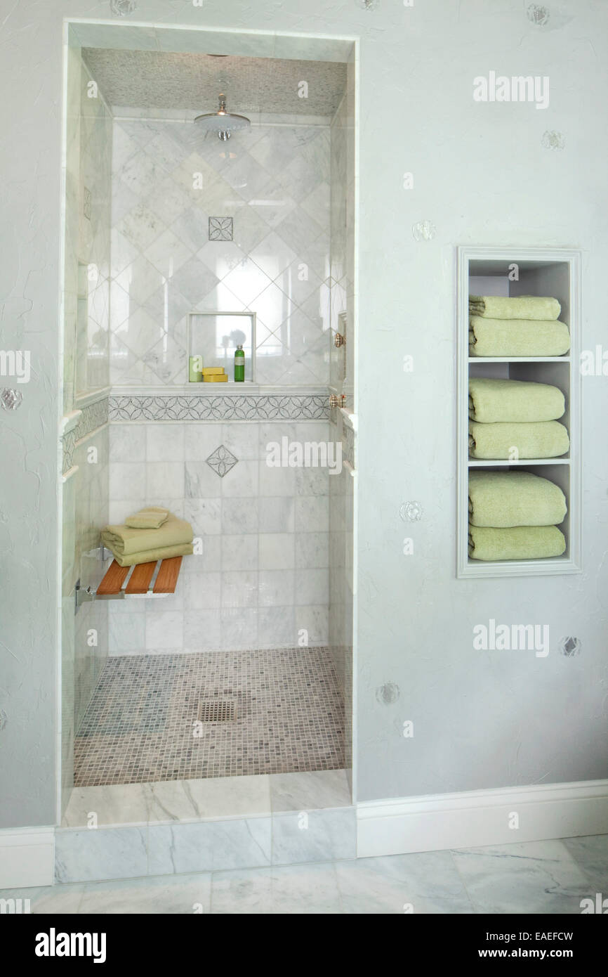 Walk In Shower With Bench And Green Towels In Bathroom Stock Photo Alamy